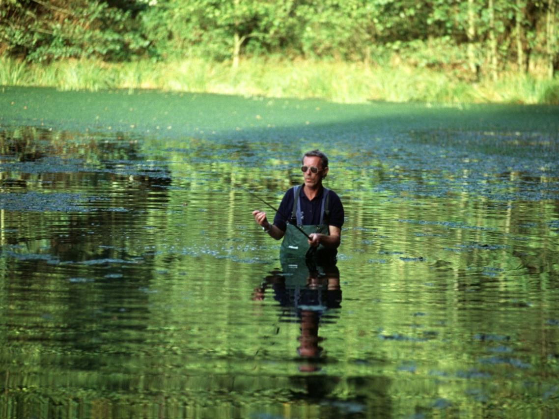Ein Angler steht mit einer Anglerhose im Wasser und angelt
