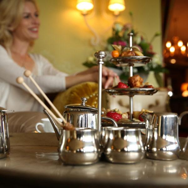 Frau bei der Tea Time mit Etagere und Teekannen