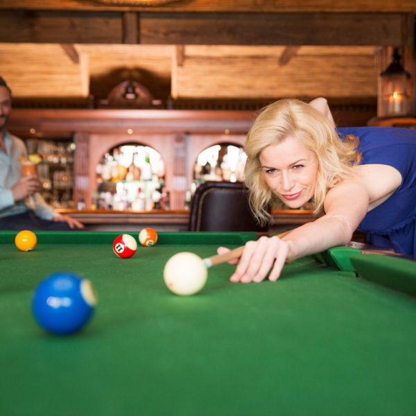 Frau spielt Billard in der Bar