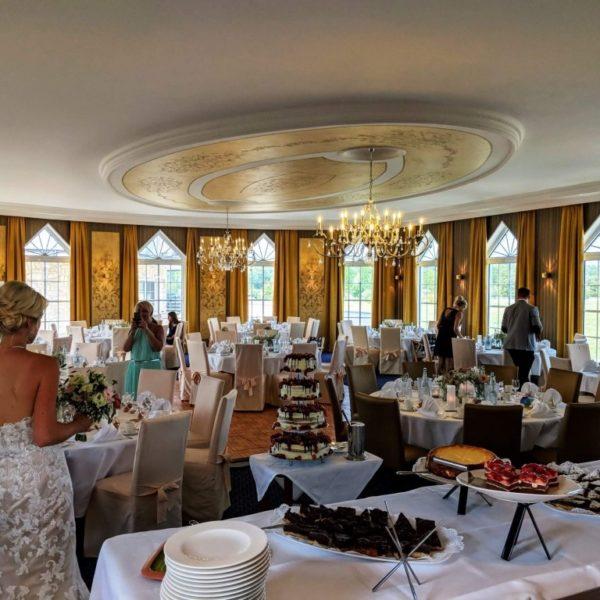 Braut vor Kuchenbuffet im Schlosssaal
