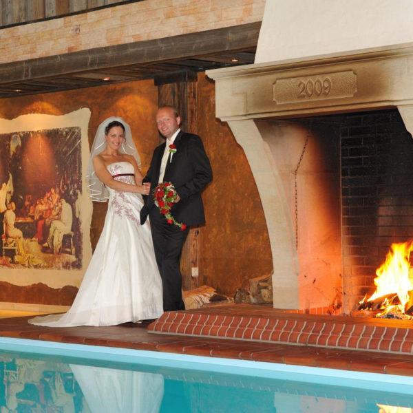 Brautpaar vor Kamin am Innenpool