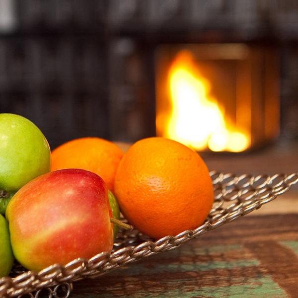 Obstschale mit Äpfeln und Orangen vor dem Kamin