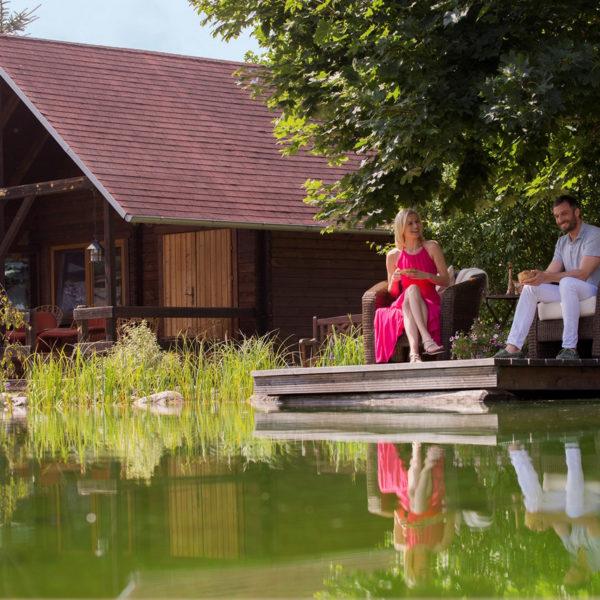 Wellnessgäste am Teich vor Holzhütten