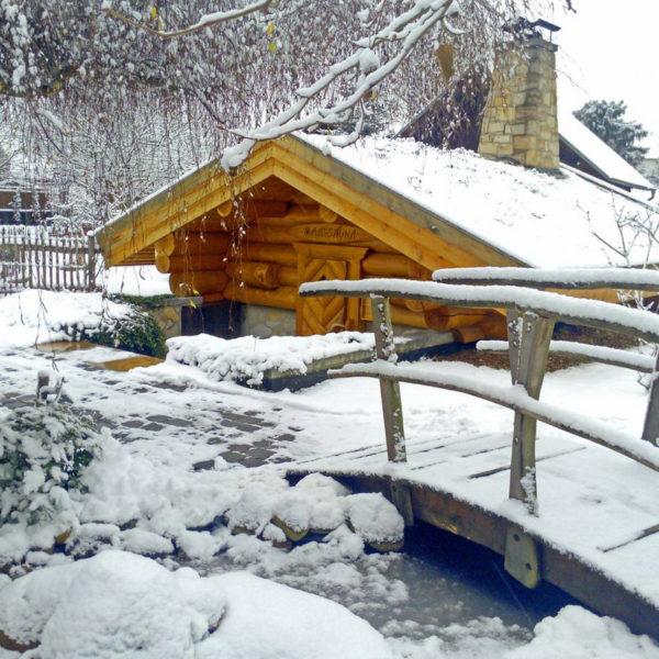 Verschneite Blockhütte der Maa-Sauna