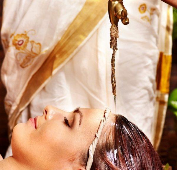 Frau bei ayurvedischen Stirnölguss